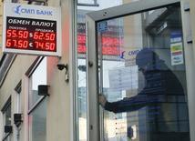 """Мужчина выходит из банковского отделения в Москве. 6 января 2015 года. Рубль дорожает утром понедельника вслед за нефтью и за счет локального выхода из безопасных активов после уикенда, при этом рыночная ликвидность может быть пониженной из-за выходного в США - Дня Колумба, в связи с чем биржевые торги парой доллар/рубль расчетами """"сегодня"""" не проводятся. REUTERS/Maxim Zmeyev"""