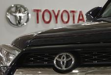 A logo of Toyota Motor Corp is pictured on a car and the background at the company's showroom in Tokyo, Japan, June 16, 2015. Toyota Motor Corp shareholders approved a controversial new class of stock on Tuesday that will bring in more long-term investors, but which faced opposition from foreign funds as they are readily available only in Japan. REUTERS/Yuya Shino