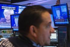 Un operador trabajando, mientras la televisión muestra a la presidenta de la Reserva Federal, Janet Yellen, en la Bolsa de Nueva York, 17 de junio de 2015. La desaceleración económica global tiene un claro riesgo de extenderse hacia el próximo año, junto con período aún más prolongado de desinflación, según una abrumadora mayoría de casi 300 economistas encuestados por Reuters en el mundo. REUTERS/Lucas Jackson