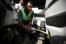 A worker fills petrol on a vehicle at the petrol pump in in Kathmandu, Nepal September 28, 2015. REUTERS/Navesh Chitrakar