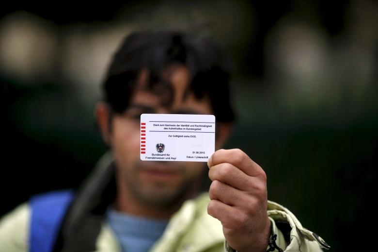 Omar, a 27-year-old cook originally from Deraa, the cradle of the Syrian uprising against Bashar Al-Assad, shows the back of his Austrian migrant card in Traiskirchen, Austria, October 13, 2015.  REUTERS/Leonhard Foeger