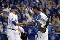 Kansas City Royals relief pitcher Wade Davis (17) and catcher Salvador Perez (13) celebrates after beating the Toronto Blue Jays in game two of the ALCS at Kauffman Stadium. Mandatory Credit: John Rieger-USA TODAY Sports