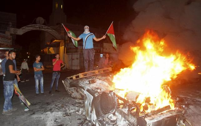 A Palestinian holding Palestinian flags stands on a burning car belonging to Jewish settlers after it was set on fire by Palestinians in the West Bank city of Nablus October 18, 2015. REUTERS/Abed Omar Qusini