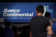 People stand outside a branch of Banco Continental, hours after the Honduran government ordered its liquidation, in Tegucigalpa, Honduras, October 12, 2015. REUTERS/Jorge Cabrera