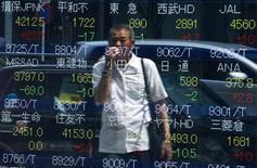 Un hombre mira el precio de las acciones, en un tablero electrónico afuera de una correduría, en Tokio, 28 de julio de 2015. El índice Nikkei de la bolsa de Tokio cayó el lunes en medio de una falta de señales comerciales positivas en el mercado doméstico, pero unos datos de China que mostraron que su economía no se enfrió tanto como se esperaba en el tercer trimestre tranquilizaron a los inversores. REUTERS/Thomas Peter