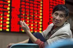Un inversor frente a un tablero electrónico que muestra la información de las acciones, en una correduría en Nanjing, China, 16 de octubre de 2015. Las acciones chinas cerraron estables el lunes luego de que una toma de ganancias en la tarde revirtió las ganancias de la mañana anotadas por los datos de crecimiento del tercer trimestre que mostraron una desaceleración gradual de la actividad económica, pero sin señales de un aterrizaje forzoso.                         REUTERS/China Daily
