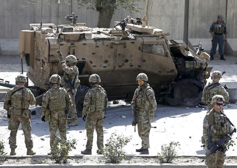 NATO soldiers stand near a damaged NATO military vehicle at the site of a suicide car bomb blast in Kabul, Afghanistan, October 11, 2015. REUTERS/Omar Sobhani