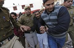 Policemen escort driver Shiv Kumar Yadav (3rd R in black jacket) who is accused of a rape outside a court in New Delhi December 8, 2014. REUTERS/Adnan Abidi/Files