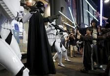 """Un niño vestido de jedi de """"Star Wars"""" juega con un hombre disfrazado de Darth Vader en el distrito comercial de Myeongdong, en Seúl, Corea del Sur, el 4 de septiembre de 2015. Los fans de """"Star Wars"""" disfrutaron el lunes del vistazo más largo a la fecha de la próxima película de la franquicia, """"The Force Awakens"""", en un trailer lleno de acción que se convirtió en el principal tema de tendencia de Twitter y provocó una avalancha de reservas que hizo colapsar a un vendedor estadounidense de entradas en línea. REUTERS/Kim Hong-Ji"""