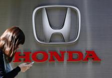 A woman using her mobile phone walks past a logo of Honda Motor Co outside the company's dealership in Tokyo October 28, 2014. REUTERS/Yuya Shino