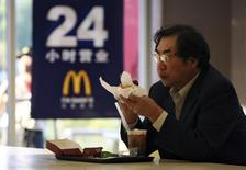 Мужчина ест в ресторане McDonald's в Шанхае. 8 ноября 2006 года. Крупнейшая в мире сеть ресторанов McDonald's Corp сообщила в четверг о росте сопоставимых продаж в третьем квартале благодаря восстановлению спроса в Китае и США. REUTERS/Nir Elias