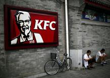 Men sits outside a KFC restaurant in Beijing in this July 17, 2014 file photo.  REUTERS/Kim Kyung-Hoon/Files