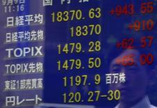 Un peatón se refleja en un tablero electrónico que muestra varios índices de acciones, en una correduría en Tokio, Japón, 9 de septiembre de 2015. Las bolsas de Asia se sumaban el viernes a un repunte global de la renta variable luego de que el Banco Central Europeo sugirió que está dispuesto a inyectar más estímulos, lo que ayudó al dólar a trepar a un nuevo máximo en dos meses frente al euro. REUTERS/Yuya Shino