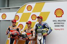 Honda MotoGP rider Marc Marquez of Spain (L), Dani Pedrosa of Spain (C) and Yamaha MotoGP rider Valentino Rossi (R) of Italy pose for photographs chat after Pedrosa won the pole position for Sunday's Malaysian Motorcycle Grand Prix at Sepang International Circuit near Kuala Lumpur, Malaysia, October 24, 2015. REUTERS/Olivia Harris