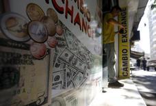 Мужчина выходит из пункта обмена валюты в Рио-де-Жанейро. 31 августа 2015 года. Курс доллара к корзине шести основных валют снижается с максимума 2,5 месяцев, хотя сокращение процентных ставок в Китае дает доллару поддержку. REUTERS/Ricardo Moraes