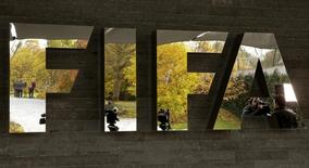 Journalists are reflected in FIFA's logo as they wait during an extraordinary meeting of the FIFA Executive Committee in front of FIFA's headquarters in Zurich, Switzerland October 20, 2015.    REUTERS/Arnd Wiegmann