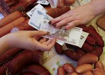 Продавец берет деньги у покупателя на рынке в Красноярске. 29 июля 2015 года. Инфляция в РФ в октябре 2015 года может составить 0,7 процента в месячном выражении, сказал заместитель министра финансов Максим Орешкин. REUTERS/Ilya Naymushin