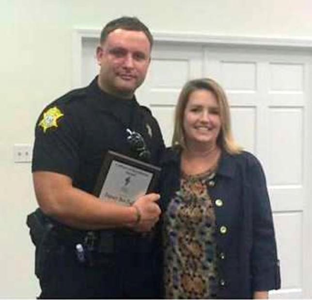 Richland County Sheriff's Department Officer Senior Deputy Ben Fields is pictured with Karen Beaman (R), Principal of Lonnie B. Nelson Elementary School after receiving Culture of Excellence Award at Lonnie B. Nelson Elementary School in Columbia, South Carolina on November 12, 2014. REUTERS/Richland County Sheriff's Department/Handout