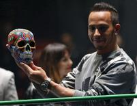 Mercedes Formula One driver Lewis Hamilton of Britain holds up at a traditional Day of the Dead Mexican skull at the Coliseo Arena during a promotional event in Mexico City, Mexico October 28, 2015. REUTERS/Henry Romero
