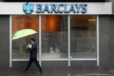 "A man shelters under umbrellas as he walks past a Barclays branch in central London May 8, 2014. Britain's Barclays will axe 19,000 jobs in the next three years and set up a ""bad bank"" to house much of its investment banking business and European retail operations as it strives to turn itself around in the face of a trading slump.    REUTERS/Stefan Wermuth (BRITAIN - Tags: BUSINESS)"