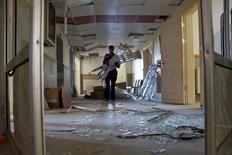 Мужчина с костылями идет по коридору попавшей под авиаобстрел больницы в провинции Дераа. 23 июля 2015 года. Как минимум 12 больниц на севере Сирии попали под авиаобстрелы за последние недели, в результате чего погибли не менее 35 пациентов и медицинских работников, сообщила международная благотворительная организация Врачи без границ. REUTERS/Alaa Al-Faqir