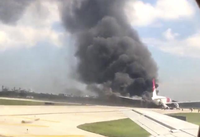 A still image from a handout video footage by Mike Dupuy, a passenger in another airplane, shows Dynamic International Airways' Boeing 767's engine on fire in Fort Lauderdale, Florida, October 29, 2015.  REUTERS/Mike Dupuy