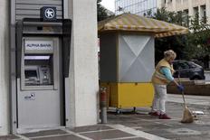 En la imagen de archivo, una mujer limpia la acera frente a un cajero de Alpha Bank en Atenas. 31 de octubre de 2015. Los bancos de Grecia necesitan 14.400 millones de euros de capital, dijo el sábado el Banco Central Europeo, tras pruebas realizadas para rehabilitar a los prestamistas del país. REUTERS/Michalis Karagiannis