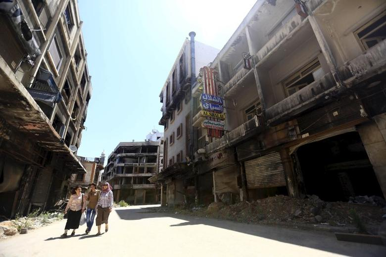 Women walk past damaged buildings along a street in the old city of Homs June 3, 2015. REUTERS/Omar Sanadiki
