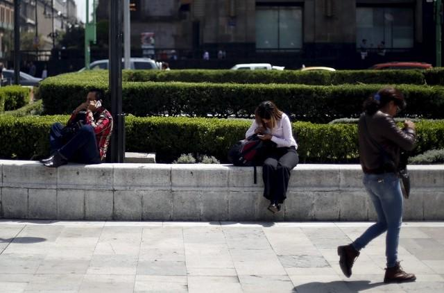 People use their cell phones in Mexico City, October 8, 2015. REUTERS/Edgard Garrido/Files