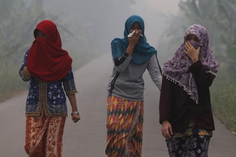 Villagers walk on a street as the haze shrouds Pulau Mentaro village in Muaro Jambi, on the Indonesian island of Sumatra, September 15, 2015. REUTERS/Beawiharta/Files