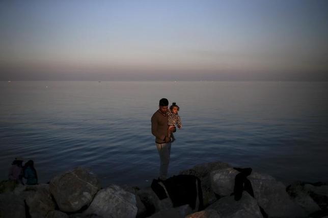 11月5日、欧州委員会は経済見通しのなかで、2017年までに300万人の難民が域外からEU加盟国にやってくると見込んだ。難民が社会の中で労働力として融合すれば、経済成長を押し上げ、長期的には財政改善につながる可能性があるとしている。写真は同日、ギリシャのレスボス島の海岸のシリア難民の親子(2015年 ロイター/Alkis Konstantinidis)