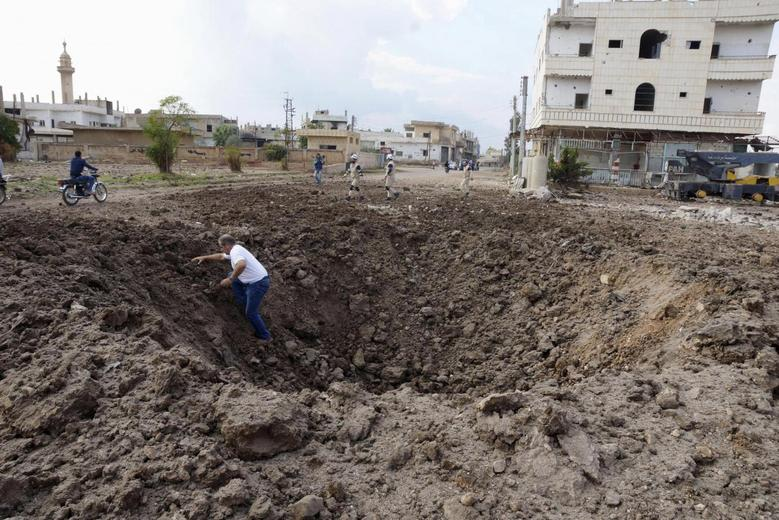 A man walks out of a crater caused by what activists said was a barrel bomb dropped by forces loyal to Syria's President Bashar Al-Assad in the town of Dael, north of Deraa, Syria November 8, 2015. REUTERS/Alaa Al-Faqir