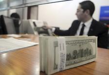 Un empleado de una casa cambiaria cuenta dólares estadounidenses en un banco en El Cairo, 31 de diciembre de 2013. El dólar aumentaba el martes hacia un máximo de siete meses frente a una canasta de monedas, impulsado por una ampliación del diferencial en favor de los bonos del Tesoro estadounidense ante la expectativa de que la Reserva Federal elevará las tasas de interés el mes que viene. REUTERS/Stringer