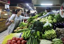 Una clienta compra vegetales en un mercado en Qingdao, China, 14 de octubre de 2015. Los datos de inflación de octubre en China revelaron una presión deflacionaria persistente, lo que instó a los analistas a esperar más medidas para estimular a la economía antes de que concluya el año. REUTERS/Stringer
