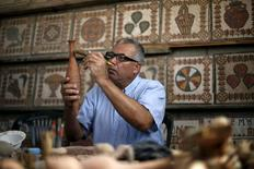 Archeology Nafez Abed cleans sculptures at his workroom, at Shati refugee camp in Gaza City, November 8, 2015. REUTERS/Suhaib Salem
