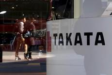 A logo of Takata Corp is seen with its display as people are reflected in a window at a showroom for vehicles in Tokyo, Japan November 6, 2015.  REUTERS/Toru Hanai  -
