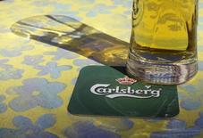 Логотип Carlsberg на бирдекеле в баре в Риге 6 мая 2013 года. Пивоваренная компания Carlsberg, испытывающая сложности в России, зарезервировала $1,4 миллиарда под обесценение активов и расходы на реструктуризацию, а также сократит 15 процентов сотрудников, не занятых на производстве, в попытке вернуться к росту. REUTERS/Ints Kalnins