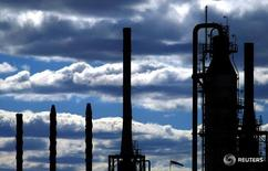 Towers at an oil refinery in the southern Sydney suburb of Kurnell are silhouetted against a cloudy sky August 6, 2004.  REUTERS/Tim Wimborne  TBW/LA -