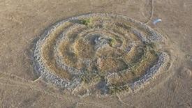 Vista general de un monumento prehistórico de piedra, conocido como Rujm el-Hiri, en los Altos del Golán, 24 de julio de 2014. Es fácil pasar de largo sin ver una de las estructuras más misteriosas de Oriente Medio. De hecho, este monumento prehistórico de piedra pasó desapercibido durante siglos en un terreno baldío en los Altos del Golán. REUTERS/Chen Katz      SÓLO DISPONIBLE PARA USO EDITORIAL.
