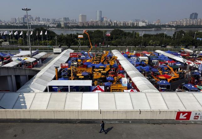 A man walks past construction vehicles on display during the China Import and Export Fair, also known as Canton Fair, in the southern Chinese city of Guangzhou October 15, 2015. REUTERS/Bobby Yip