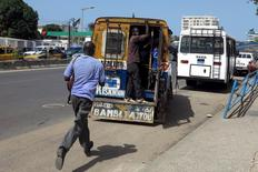 "A man runs to catch a ride on a ""car rapide"" in Dakar, Senegal, October 29, 2015. REUTERS/Makini Brice"