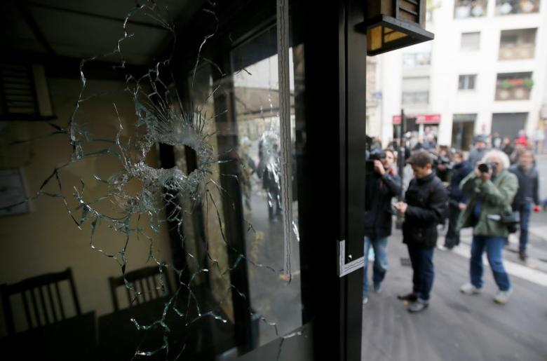 Journalists work outside a restaurant where bullet impacts are seen in the shop window the day after a series of deadly attacks in Paris, France, November 14, 2015.  REUTERS/Gonzalo Fuentes