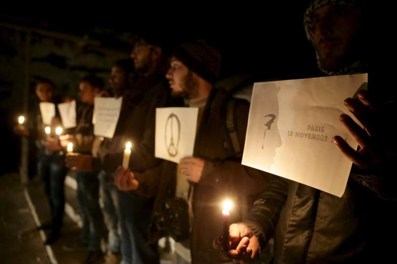 Residents carry candles and placards in tribute to the victims of the Paris attacks in the town of Duma, eastern Ghouta in Damascus November 14, 2015. REUTERS/Bassam Khabieh