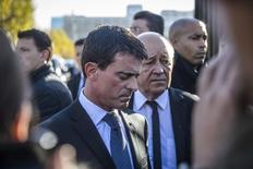 Премьер-министр Франции Мануэль Вальс (слева) и министр обороны Жан-Ив Ле Дриан. Париж, 15 ноября 2015 года. Французская полиция минувшей ночью провела обыски в домах подозреваемых боевиков-исламистов после серии атак, произошедших в пятницу вечером в Париже, сказал в понедельник премьер-министр Мануэль Вальс, указав на возможность новых атак. REUTERS/Christophe Petit Tesson/Pool