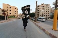 """Боевик с флагом ИГ в Эр-Ракке. 29 июня 2014 года. """"Исламское государство"""" предупредило в видеообращении, распространённом в понедельник, что страны, принимающие участие в воздушной операции против ИГИЛ в Сирии, постигнет та же участь, что и Францию, и пообещало нанести удар по Вашингтону. REUTERS/Stringer"""