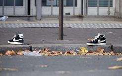 Пара кроссовок у концертного зала Bataclan в Париже. 14 ноября 2015 года. Сообщения о том, что находящийся сейчас в Сирии гражданин Бельгии Абдельхамид Абаауд является организатором атак в Париже - неподтверждённые слухи, сообщила прокуратура Бельгии. REUTERS/Charles Platiau