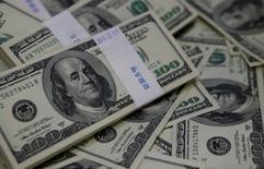 Fajos de billetes de 100 dólares en un banco en Seúl, 2 de agosto de 2013. El dólar subía el lunes frente a varias monedas importantes, debido a que los mercados están cada vez más convencidos de que la Reserva Federal subirá las tasas de interés el próximo mes, al tiempo que se redujo el temor de los inversores tras los ataques del viernes en París. REUTERS/Kim Hong-Ji