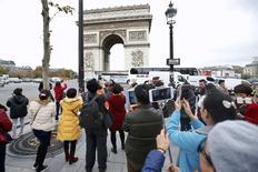 Touristes devant l'Arc de Triomphe. Le taux d'occupation des hôtels parisiens a accusé une forte baisse samedi et dimanche au lendemain des attentats qui ont frappé la capitale, selon des données collectées par la société de conseil MKG Hospitality. /Photo prise le 16 novembre 2015/REUTERS/Charles Platiau