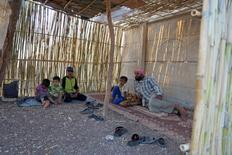 Abu Ahmad (R) rests with his children in a temporary summer room he built within a refugee camp that was formerly the Zeyzoun Vanguards summer camp for school children in Zeyzoun village, Deraa region, Syria, August 6, 2015. REUTERS/Alaa Al-Faqir - RTS6SRR