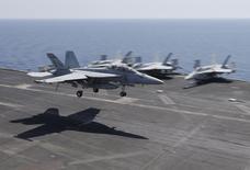"""Самолет F/A-18E/F совершает посадку на палубу американского авианосца """"Теодор Рузвельт"""". 18 июня 2015 года. Большинство американцев хотят, чтобы США усилили борьбу с """"Исламским государством"""" после атак в Париже, однако также большинство остаются против отправки войск в Ирак или Сирию, где базируется группировка, показали результаты опроса, проведенного Рейтер и социологической службой Ipsos. REUTERS/Hamad I Mohammed"""